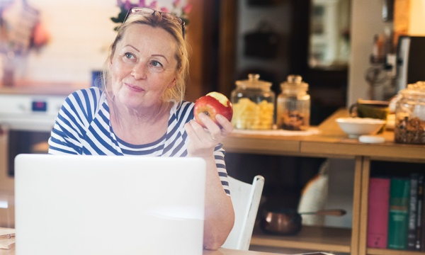 Woman eating apple at her laptop